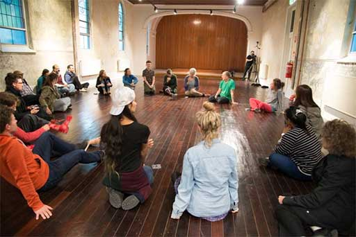 audience and performers sit in a circle discussing participatory performance experience