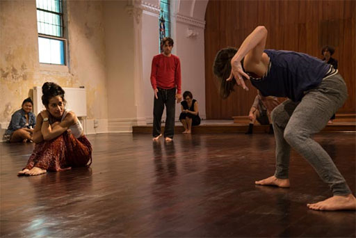 a participatory performance with performers and audience members sitting, standing and moving in the performance space