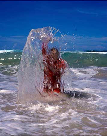 a person standing in shallow water at the beach splashes water into the air while a wave approches from behind