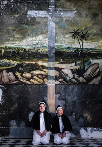 Two performers wearing nuns habits seated in front of a painted cross