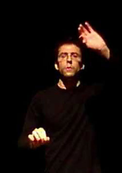 A man dressed in black holds his hands in the air as if conducting and orchestra.