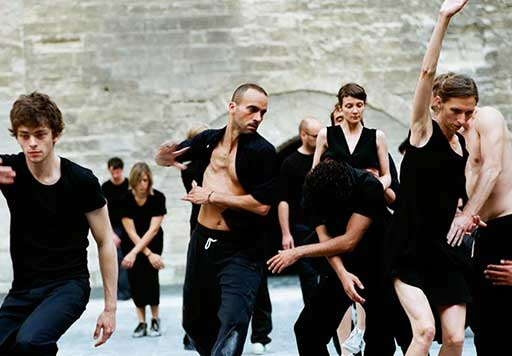 A group of 10 dancers dressed casually in black t-shirts, pants and sneakers performing in front of an old brick wall