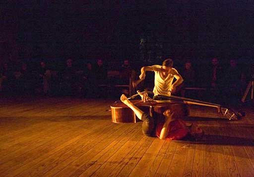 A female dancer lies on her back embracing a cello between her legs, which is bing played by a male performer.