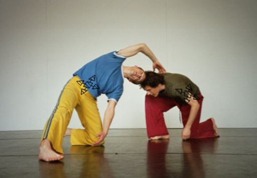 Two men dancing in a studio, both bend and kneel with one reaching over to touch the others back.