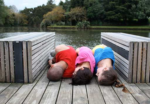 Three dancers lie back-to-back between benches on a deck next to a lake.