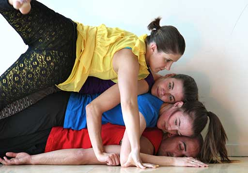 Four dancers lie stacked on top of each other.