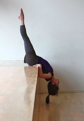 Balancing upside down on her lower back over the edge of a table.