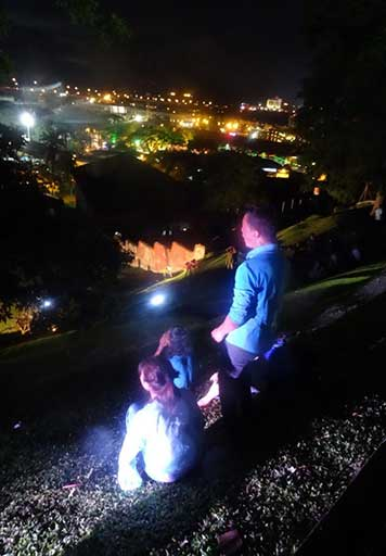 The performers view from above the hilly site to the night-time cityscape below.