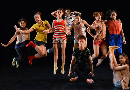 A group of 10 young colourfully dressed Taiwanese dancers jumping with joy.