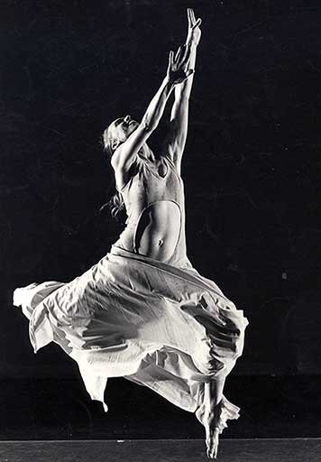 A black and white photo of Elizabeth Cameron Dalman jumps high in the air, head stretched back, with arms reaching above her. She is smiling.