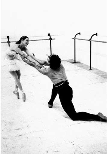 Marilyn Jones on pointe and wearing a white tutu, leans over arms outstretched towards Jonathan Kelly who kneels before her clasping her arms.