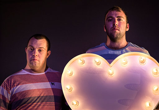 Two men stand side-by-side looking straight at us. Both dressed casually in striped t-shirts, the taller holds a large cut-out heart shape outlined with studded lit incandescent light bulbs