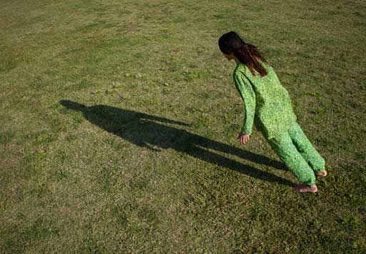 Female dancer dressed in green leans towards her own shadow cast across the grass.