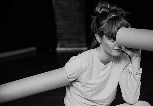 Dancer/choreographer Sarah Aitkin looks through a cardboard tube