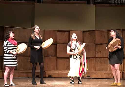Four performers onstage singing and playing percussive instruments.