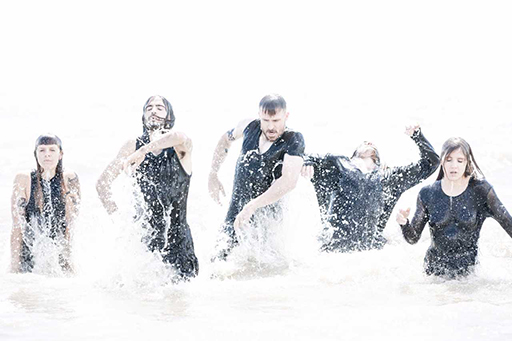 Five Dancenorth dancers walk out of the sea through rough waves.