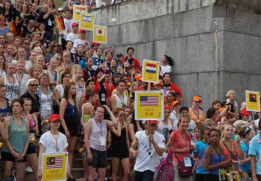Over 100 World Dance Alliance Global Summit 2012 participants on university entrance staircase holding country flags.